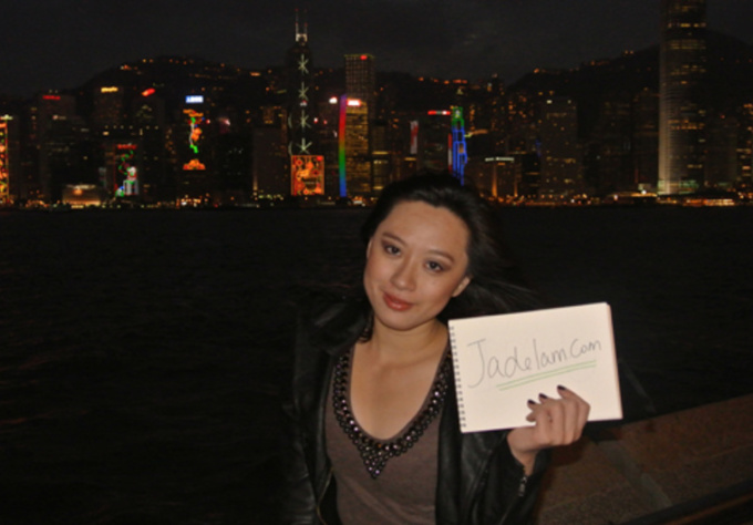 take photos holding your sign in front Victoria Harbour, Hong Kong